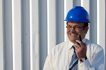 an industrial engineer wearing a blue hard hat, talking on a radio